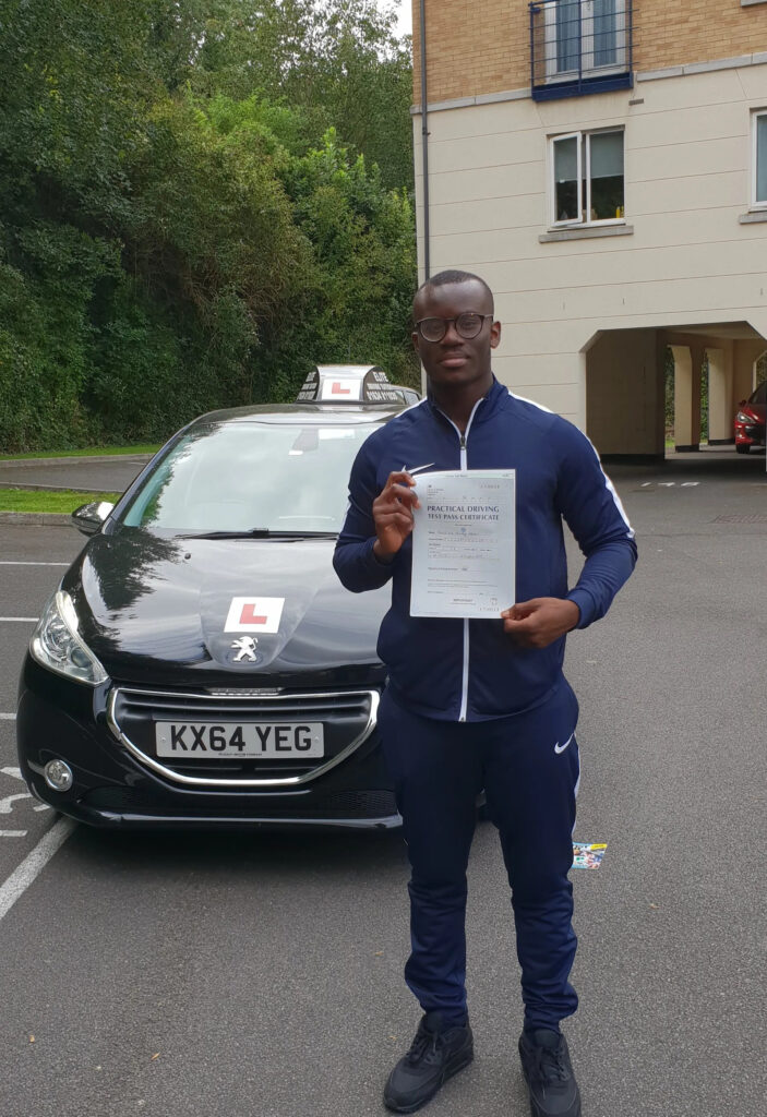 Pupil standing in front of black car holding pass certificate